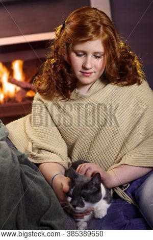 Teenage girl sitting at fireplace at home caressing cat affectionate.