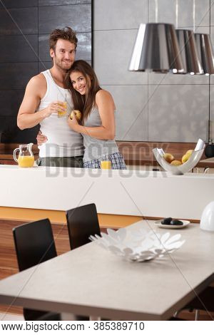Portrait of happy loving couple in the morning at the kitchen.