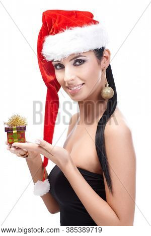 Attractive woman in santa hat holding small Christmas box, wearing Christmas ornament in ear, smiling, looking at camera.