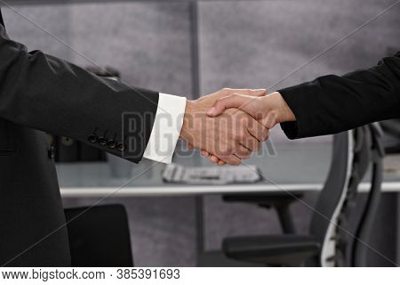 Businessman and businesswoman shaking hands.