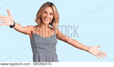 Beautiful caucasian woman wearing summer dress looking at the camera smiling with open arms for hug. cheerful expression embracing happiness.