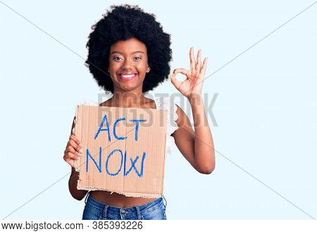 Young african american woman holding act now banner doing ok sign with fingers, smiling friendly gesturing excellent symbol