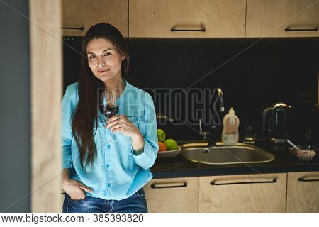 Lady With A Wineglass Leaning Against The Countertop