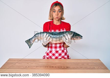 Beautiful caucasian woman fishmonger selling fresh raw salmon puffing cheeks with funny face. mouth inflated with air, catching air.