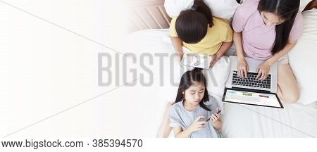 Top View Asian Mother And Daugthers Looking Laptop, Smart Phone And Tablet On Bed In Bedroom. Busine