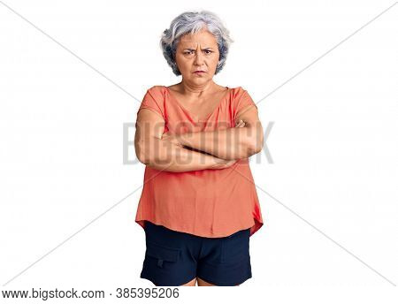 Senior woman with gray hair wearing orange tshirt skeptic and nervous, disapproving expression on face with crossed arms. negative person.