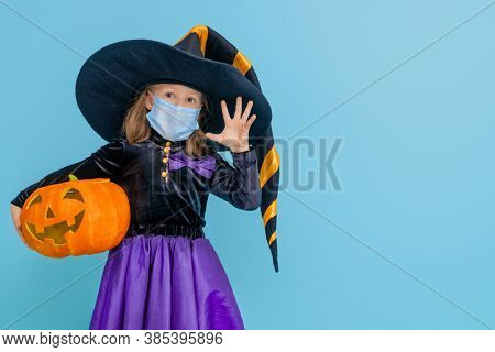 Happy Halloween! Cute little witch with a pumpkin  wearing face mask protecting from COVID-19.