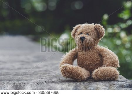Teddy Bear With Sad Face Sitting On Footpath Blurry Background, Loneliness Brown Bear Doll Sitting A