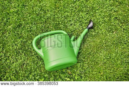 gardening and tools concept - green watering can on grass at summer garden