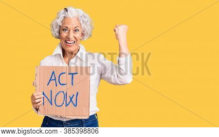 Senior grey-haired woman holding act now banner screaming proud, celebrating victory and success very excited with raised arms