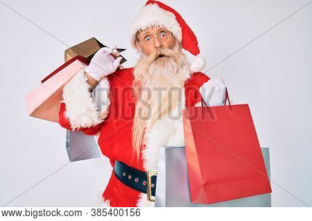 Old senior man with grey hair and long beard wearing santa claus costume holding shopping bags in shock face, looking skeptical and sarcastic, surprised with open mouth