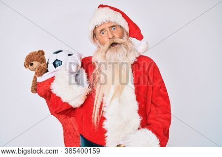 Old senior man with grey hair and long beard wearing santa claus costume holding mustache in shock face, looking skeptical and sarcastic, surprised with open mouth