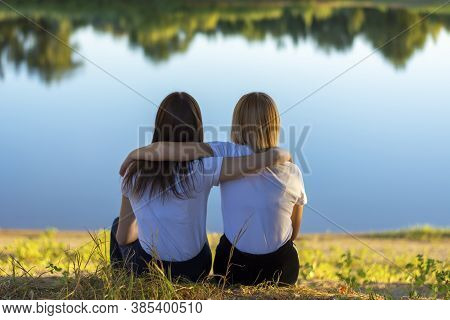 Two Young Women Rear View Hugging While Sitting On The Grass Near The River In Autumn. Friends Leane