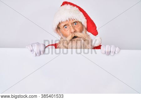 Old senior man with grey hair and long beard wearing santa claus costume holding banner in shock face, looking skeptical and sarcastic, surprised with open mouth