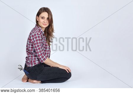 Young Beautiful Female With Dark Brown Hair And Eyes Sits On The Floor On Her Knees, The Wrench In T