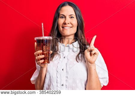 Beautiful brunette woman drinking cola refreshment beverage using straw over red background smiling happy pointing with hand and finger to the side