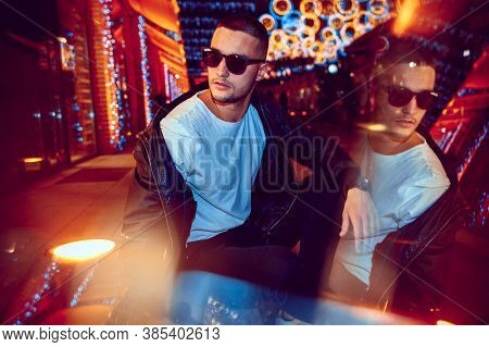 Reflection. Cinematic Portrait Of Stylish Young Man In Neon Lighted Room. Bright Neoned Colors. Cauc