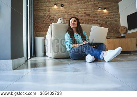 Pensive Woman Sitting Cross-legged On The Tile Floor