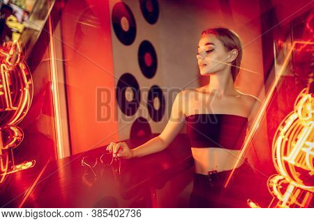 Celebrities. Cinematic Portrait Of Stylish Young Woman In Neon Lighted Room. Bright Neoned Colors. C
