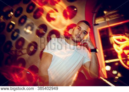 Multi Platinum. Cinematic Portrait Of Stylish Young Man In Neon Lighted Room. Bright Neoned Colors.