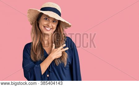 Middle age hispanic woman wearing summer hat cheerful with a smile of face pointing with hand and finger up to the side with happy and natural expression on face