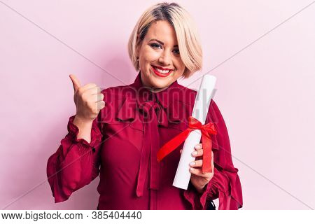 Beautiful blonde plus size woman holding graduated degree diploma over pink background smiling happy and positive, thumb up doing excellent and approval sign
