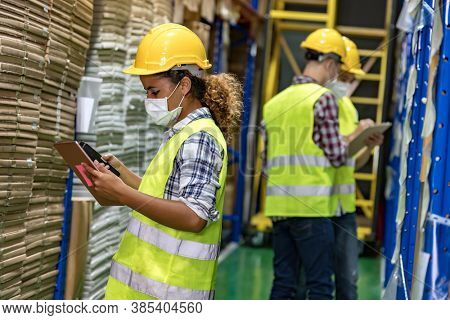 African black warehouse worker with face mask checking goods use digital tablet and barcode scanner with her interracial team working in background. They wear face mask prevent from COVID-19.