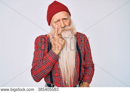 Old senior man with grey hair and long beard wearing hipster look with wool cap pointing to the eye watching you gesture, suspicious expression