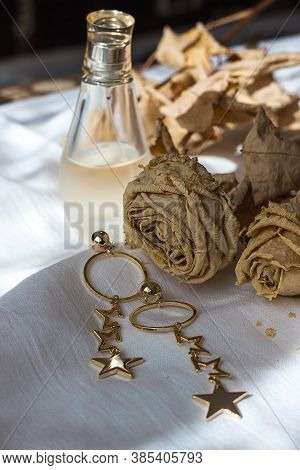 Beautiful Pendant Earrings Gold Perfume And Dried Roses On A White Bed, Contrasting Shades Of Cream-