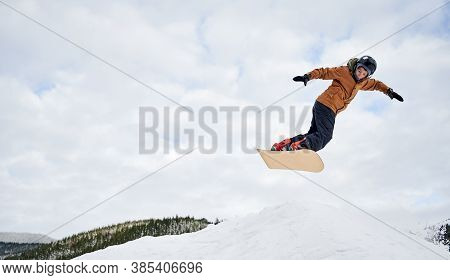 Concept Of Extreme Kinds Of Sport. Snowboarder Wearing Colorful Clothing Flying Up High With Snowboa