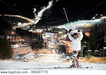 Full Length Of Male Skier In Winter Ski Jacket And Helmet Raising Ski Poles And Looking At Camera. Y