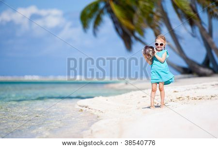 Little girl with coconut on a beach at tropical island