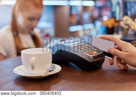 Customer Paying For Cup Of Coffee With Card, Using Terminal For Paying, White Cup Of Coffee And Red
