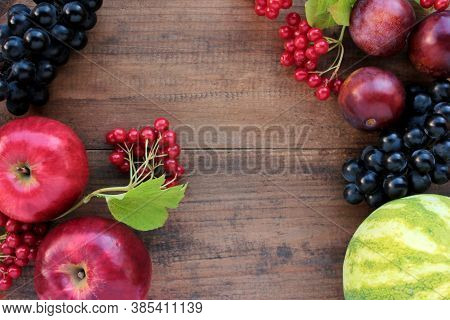 Natural Frame Made Of Grapes, Watermelon, Plums, Red Viburnum Berries, And Apples On Wooden Table. A