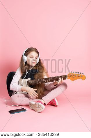Music Lessons: A Schoolgirl Learns To Play The Electric Guitar.