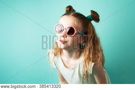 Bright Colors: A Girl In Sunglasses On A Green Background.