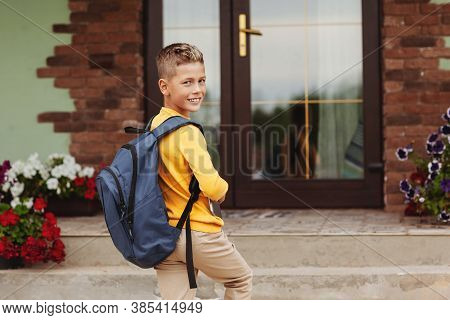 A Smiling Boy With A Briefcase And A Tablet In His Hands Stands Near His House. Ready To Go To Schoo