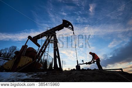 Silhouette Of Petroleum Operator In Work Vest And Helmet Using Oil Pumping Unit To Extract Crude Oil