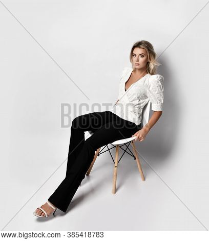 Young Sexy Blonde Slim Woman Model In Shirt, Trousers And Shoes Sitting On Chair And Looking At Came