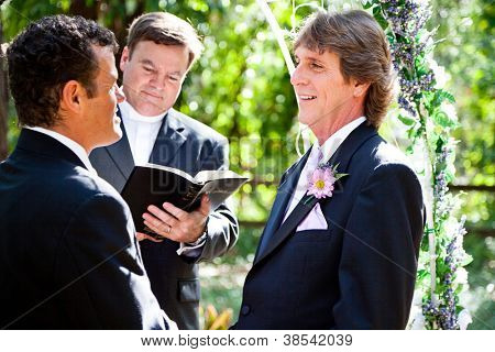 Handsome groom looks lovingly into his partner's eyes during their wedding ceremony.