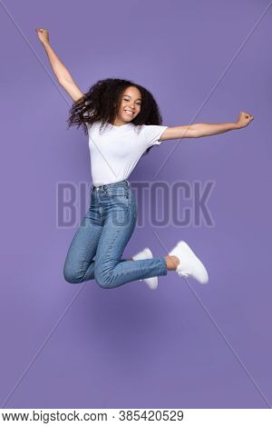 Happy African American Woman Jumping Posing In Mid-air Over Purple Studio Background, Smiling To Cam