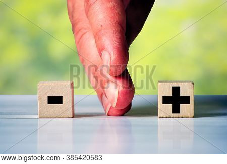 The Hand Divides Two Wooden Blocks With The Words Plus And Minus
