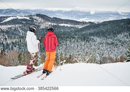 Two Friends Wearing Ski Suits And Ski Equipment Are In Winter Mountains Enjoying Snowy Weather, Skii