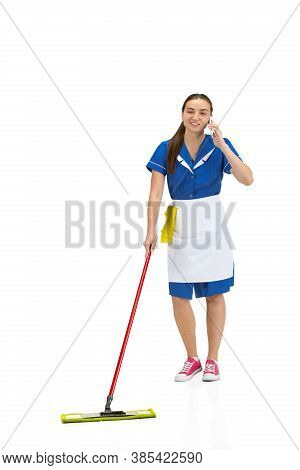Talking Phone. Portrait Of Female Made, Housemaid, Cleaning Worker In White And Blue Uniform Isolate