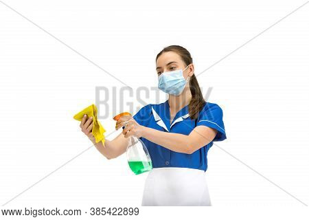 Using Cleaner And Face Mask. Portrait Of Female Made, Housemaid, Cleaning Worker In White And Blue U