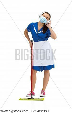 Working With Music. Portrait Of Female Made, Housemaid, Cleaning Worker In White And Blue Uniform Is