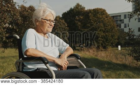 Senior Disabled Woman Sitting In The Wheelchair In The Park Enjoying Autumn Breeze. High Quality Pho