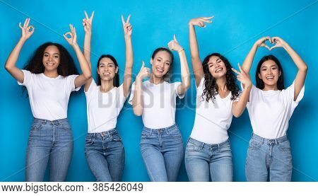 Five Positive Young Women Gesturing Different Signs Having Fun Posing Over Blue Background, Smiling