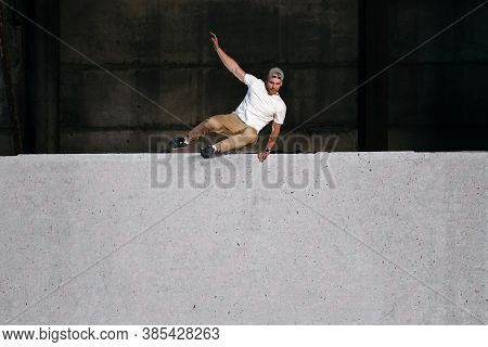 Young Strong Parkour And Freerunning Athlete Jumping Over The Wall In Urban Environment. Copy Space.