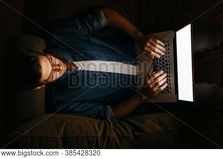 Young Programmer In Eyeglasses Working On Laptop Late At Night, Laying On Sofa At Home, Writing Text